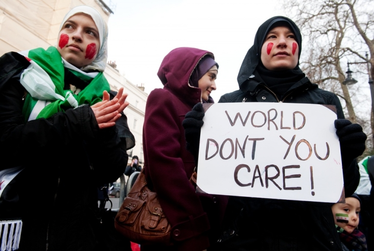 <p>A protester holds a sign during a demonstration against the regime of Syria's president, Bashar al-Assad, and his crackdown on pro-democracy protests on Feb. 4, 2012 in London.</p>