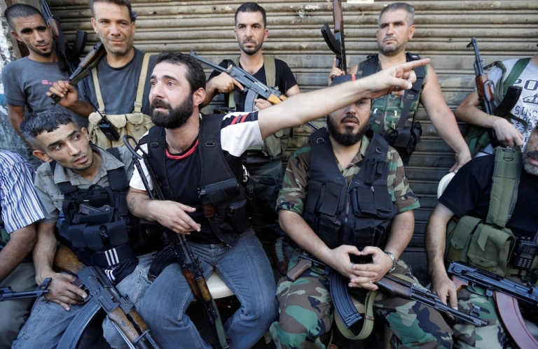<p>An anti-Damascus regime supporter expresses his anger over the death of a civilian, while his comrades rest from fighting, in the Bab al-Tabbaneh neighbourhood of the northern Lebanese port city of Tripoli, on August 22, 2012.</p>
