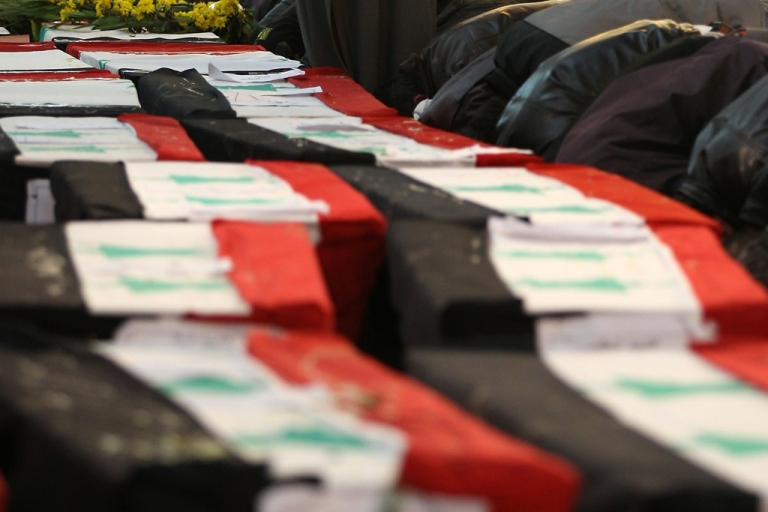 <p>Coffins draped in Syrian flags at the funeral of 44 people killed in twin suicide bombings in Damascus on Dec. 24, 2011. GlobalPost uncovered mass killings in Saqba, just outside Damascus, after a crackdown by Syrian forces.</p>