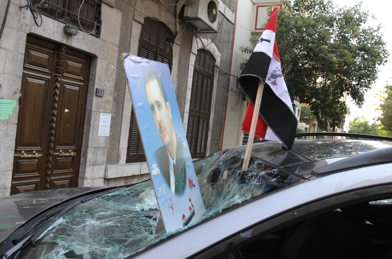<p>Pro-regime protesters planted the image of President Bashar al-Assad and the Syrian flag through the windscreen of a damaged vehicle as they gathered outside the French Embassy in Damascus on July 11, 2011</p>