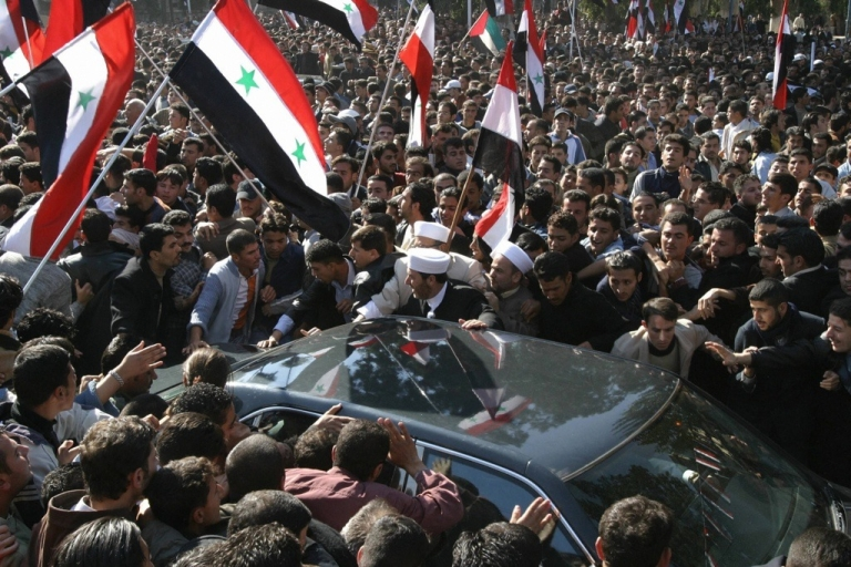 <p>Syrian people gather around the car of their president Bashar al-Assad to greet him after his speech at Damascus University on November 10, 2005.</p>
