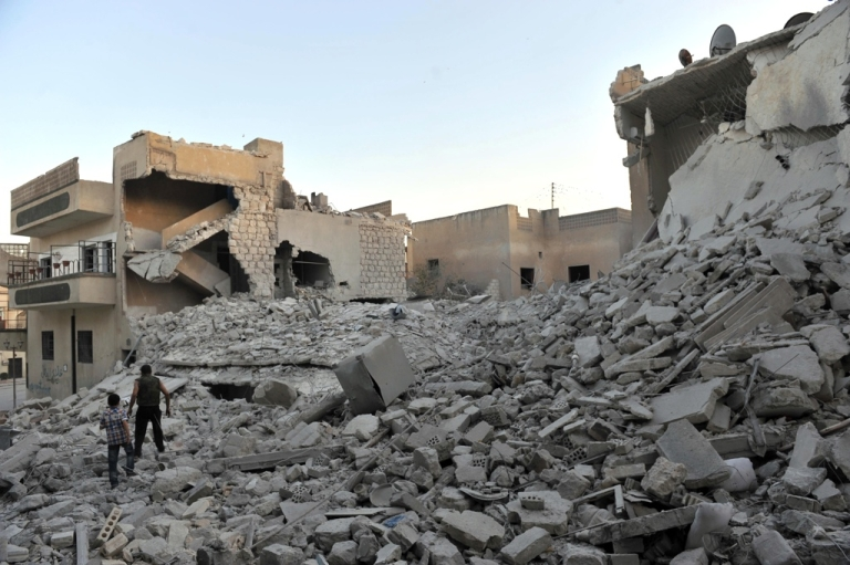 <p>Residents walk among the rubble of the ruined city of Maarat al-Nu'man in northwestern Syria.</p>