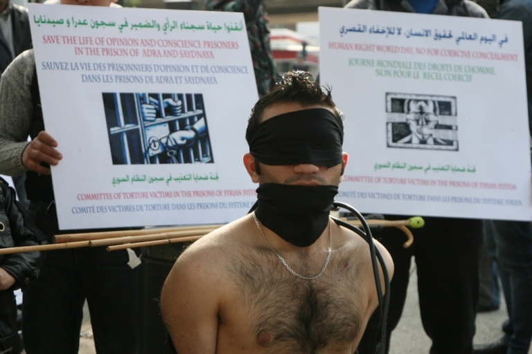 <p>A Syrian protestor mocks being tortured during a sit-in to mark International Human Rights Day, outside the United Nations offices in downtown Beirut on December 10, 2009. The demonstrators were protesting against what they said were torture methods used in Syrian prisons.</p>