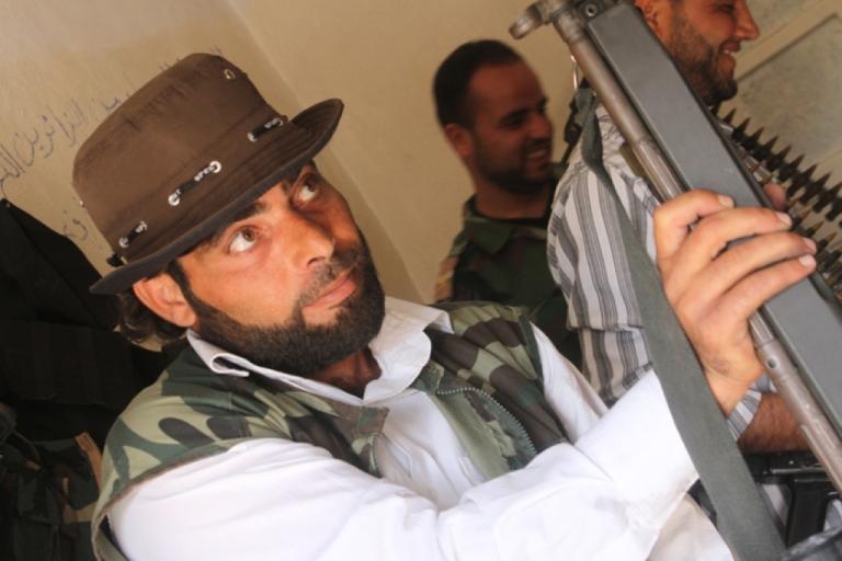 <p>Abu Ibrahim, a Free Syrian Army rebel, examines a new gun purchased from corrupt regime officials at the Al Muhajereen Wal Ansar rebel base in Jabal al-Zawiya.</p>