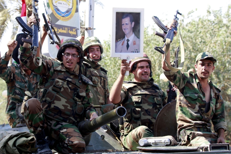 <p>THIS PICTURE WAS TAKEN ON A GUIDED GOVERNMENT TOUR<br /> Syrian soldiers raise their weapons while holding a picture of Syrian President Bashar al-Assad as they leave the eastern Syrian city of Deir Zor fon August 16, 2011.</p>