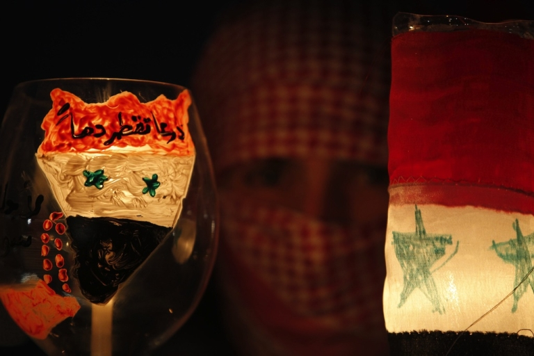 <p>Syrians living in Jordan hold candles during a protest in front of the Syrian Embassy in Amman on April 9, 2011.</p>