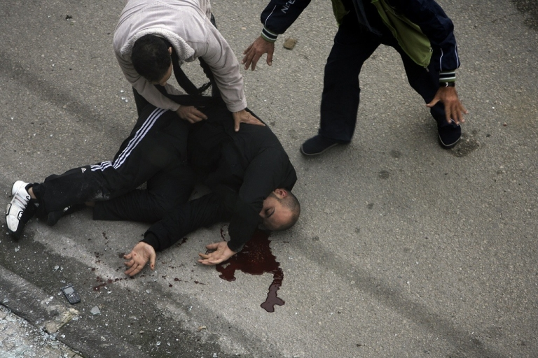 <p>A seriously injured Syrian man lies on the ground following a rocket attack in on January 11, 2012, in the western city of Homs.</p>