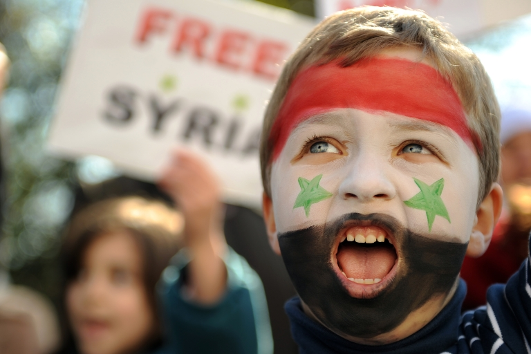 <p>A boy, whose face is painted in the colors of the Syrian flag, shouts during a demonstration against Syrian president Bashar al-Assad's rule, outside the Syrian embassy in central London, on March 19, 2011.</p>