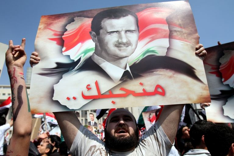 <p>Syrians chant slogans as they rally to show their support for President Bashar al-Assad (portrait), who is facing unprecedented domestic pressure amid a wave of dissent, in Damascus on March 29, 2011.</p>