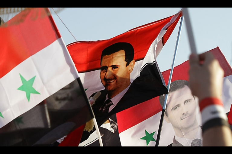 <p>A depiction of Syrian President Bashar al-Assad on the country's national flag.</p>