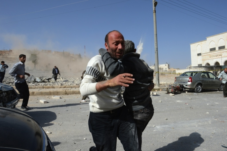 <p>A Syrian man holding a boy runs for cover as a second bomb explodes near the northern Syrian town of Al-Bab, 40 kilometers north-east of Aleppo on Nov. 4, 2012. An AFP correspondent reported three air strikes in close succession on Al-Bab.</p>