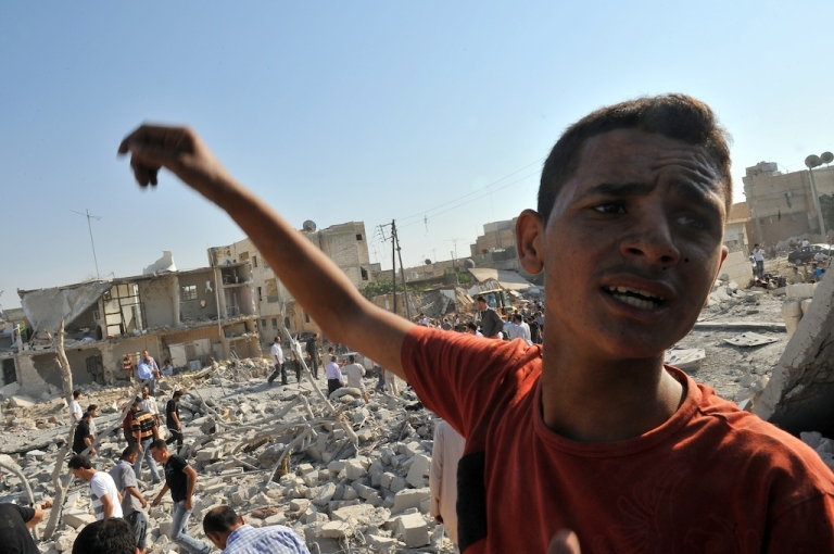 <p>A Syrian boy reacts as they look for people trapped under the rubble following an air strike in the town of Azaaz, near the northern restive Syrian city of Aleppo, on Aug. 15, 2012. UN investigators said the Syrian regime had committed crimes against humanity, as at least 20 people were reported killed in a major air strike in a rebel bastion in the north.</p>