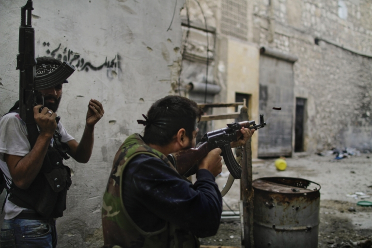 <p>Free Syria Army (FSA) fire towards regime loyalist soldiers during a battle to dislodge a sniper from its position overlooking the two main roads in the neighbourhood of Askar in Syria's northern city of Aleppo on October 24, 2012.</p>