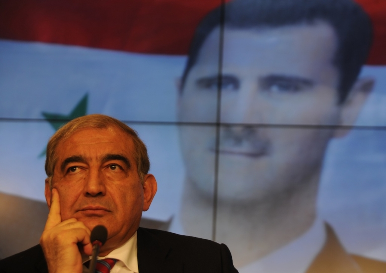 <p>Former Syrian deputy premier Qadri Jamil at a press conference in Moscow on August 21, 2012, with a picture of Syrian President Bashar al-Assad in the background.</p>