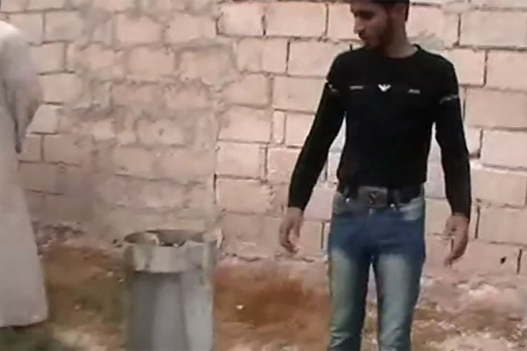 <p>A Syrian man shows the tailfin of what Human Rights Watch says is a cluster bomb.</p>