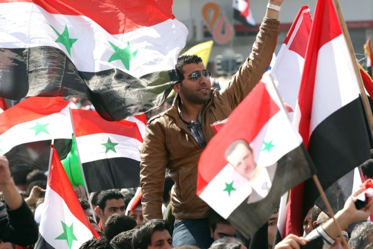 <p>Syrian flags are waved as people take to the streets after voting on a new constitution that could end five decades of single-party domination, in the capital Damascus, on February 26, 2012, although the opposition has called a boycott as the regime's bloody crackdown shows no sign of easing.</p>
