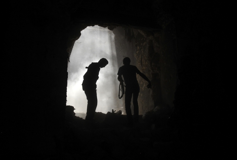 <p>Syrian rebels take cover during clashes with regime forces at the Umayyad Mosque in the old city of Aleppo hours before the Syrian army retook control of the complex on October 14, 2012.</p>