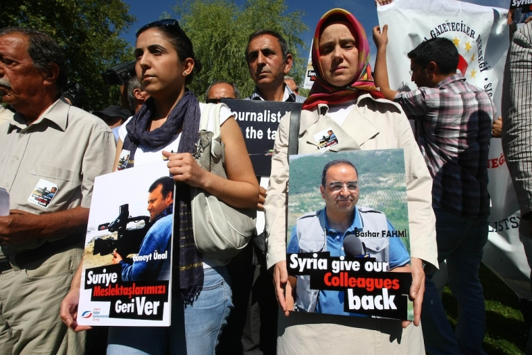 <p>Nuran Unal (C) and Arzu Fahmi (R) hold portraits of their husbands, cameraman Cuneyt Unal (C) and TV correspondent Bashar Fahmi (R), as they demonstrate in front of the Syrian Embassy in Ankara on August 31, 2012, to demand their release.</p>