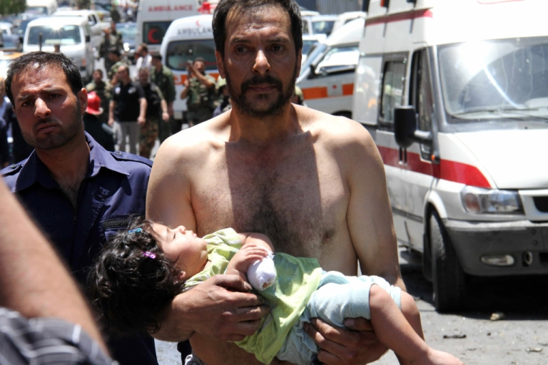 <p>A Syrian man carries a wounded girl next to Red Crescent ambulances following an explosion that targeted a military bus near Qudssaya, a neighborhood of the Syrian capital, on June 8, 2012.</p>