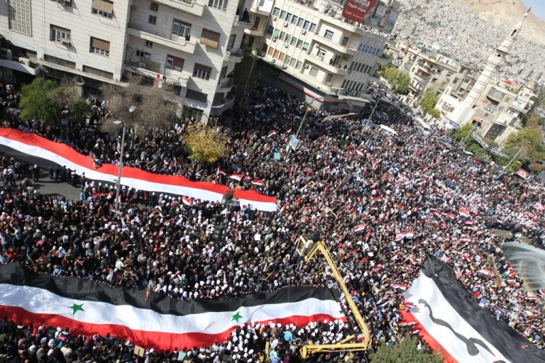 <p>Huge national flags are seen as Syrian's rally to show their support for their President Bashar al-Assad in the capital in Damascus on November 13, 2011, a day after the Arab League suspends Syria until President Bashar al-Assad implements an Arab deal to end violence against protesters, calling for sanctions and transition talks with the opposition.</p>