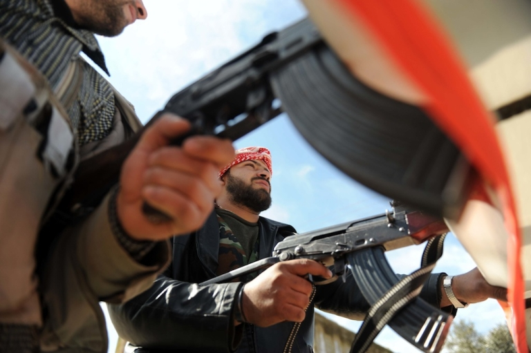 <p>Militants with the Free Syrian Army sit in the back of pick-up truck in the northwestern city of Idlib, on February 21, 2012. Syrian forces blitzed opposition hubs and opened fire to disperse daring protesters in the capital, monitors said, as the Red Cross sought ways to deliver aid to afflicted areas.</p>