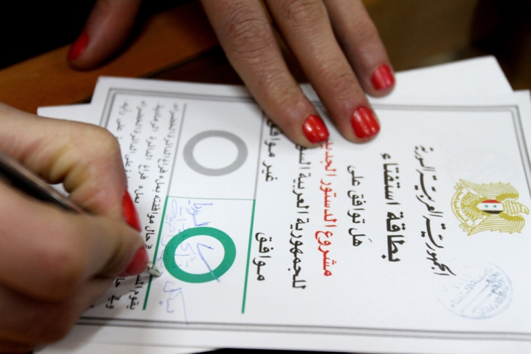 <p>A Syrian woman checks 'Agree' on a ballot card and adds 'Definitely yes for a democratic Syria' before casting her vote on a new constitution at a polling station in Damascus on February 26, 2012.</p>
