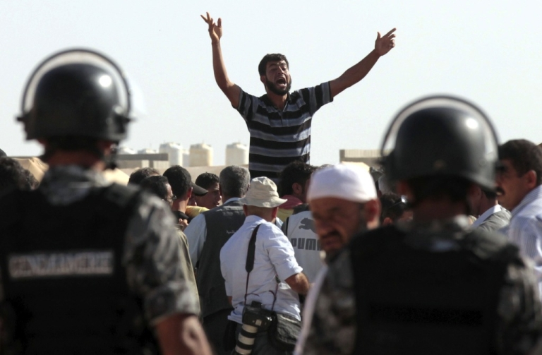 <p>Syrian refugees protest as UN Syria peace envoy Lakhdar Brahimi arrives at the at Zaatri refugee camp, home to some 30,000 Syrians, on Sept. 18, 2012. The envoy traveled from Turkey, where he also visited refugees.</p>