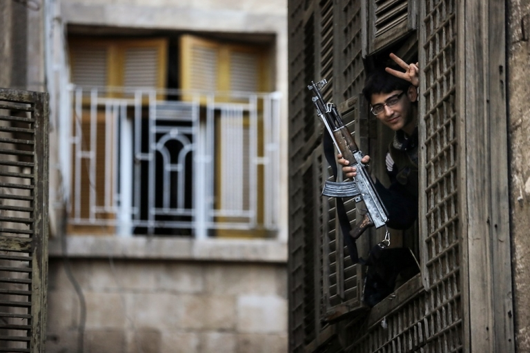 <p>A Syrian university student-turned-rebel makes a victory sign from his post in an ancient building located just 50 metres from the base of Aleppo's citadel in northern Syria on Nov. 8, 2012.</p>