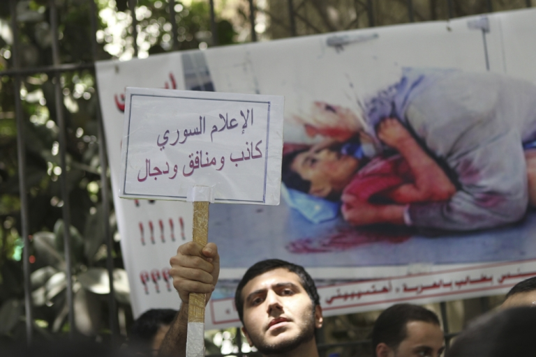 <p>Dozens of Syrian residents in Egypt protest in support of the opposition in their country in front of the Arab League headquarters in Cairo on May 5, 2011 as activists in Syria vowed a 'Day of Defiance' on Friday to press a seven-week-old anti-regime campaign in which 607 people have died, according to human rights groups, while 8,000 people have been jailed or gone missing. Arabic writing on placard reads 'Syrian media is full of lies'.</p>