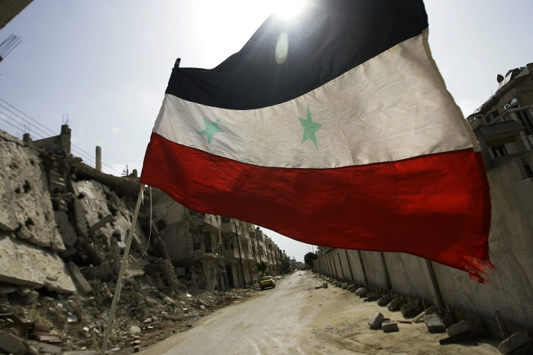 <p>A Syrian flag flutters outside a military barrack, devastated by fighting between opposition forces and Syrian troops on May 2, 2012.</p>