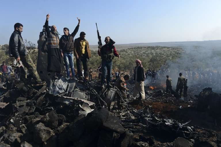 <p>Syrian rebels celebrate on top of the remains of a Syrian government fighter jet which was shot down at Daret Ezza, on the border between the provinces of Idlib and Aleppo, on November 28, 2012.  Syrian rebels captured a pilot manning the fighter jet downed over Daret Ezza in the northern province of Aleppo, witnesses told an AFP reporter in the town.</p>