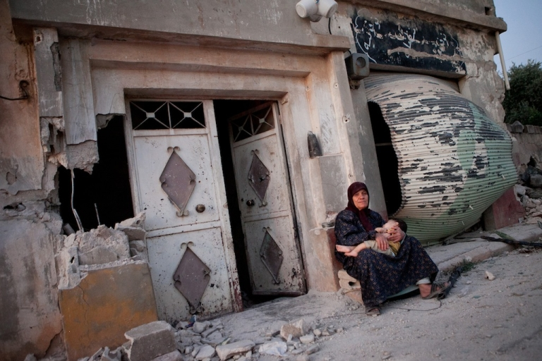 <p>A Syrian woman sits with her grandson outside a damaged building on the main street of the Syrian village of Treimsa, where more than 150 people were killed this week, in the central province of Hama on July 13, 2012. A variety of weapons were used in the attack on Treimsa, with the homes of rebels and activists bearing the brunt, UN observers said.</p>