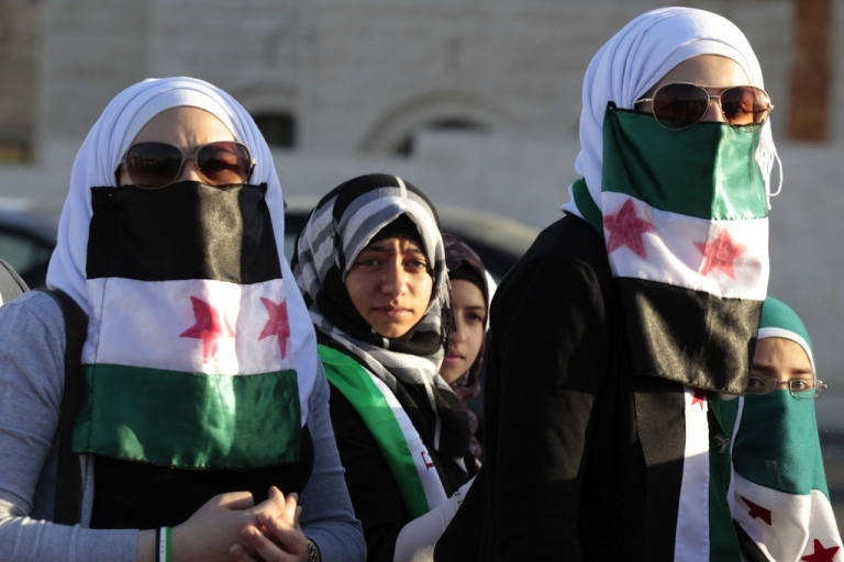 <p>Syrian women living in Jordan use the old Syrian flag adopted by the Syrian opposition groups to cover their mouths during a demonstration against Syria's President Bashar al-Assad and his regime as they gather in front of the prime minister's offices in Amman on June 13, 2012.</p>
