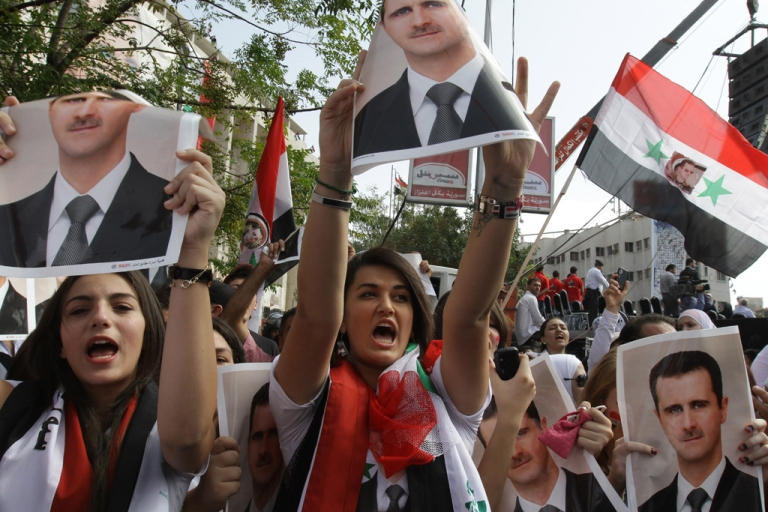 <p>Supporters of Syrian President Bashar al-Assad hold his pictures during a pro-regime rally in Damascus on October 12, 2011. Assad's regime is facing international pressure amid a violent crackdown on anti-government protests that broke out in March across Syria. (LOUAI BESHARA/AFP/Getty Images)</p>