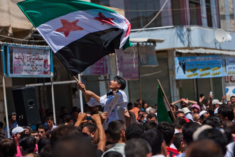 <p>A Syrian youth waves the Syrian revolutionary flag during an anti-government demonstration in the rebel-controlled northern countryside city of Mareh.</p>