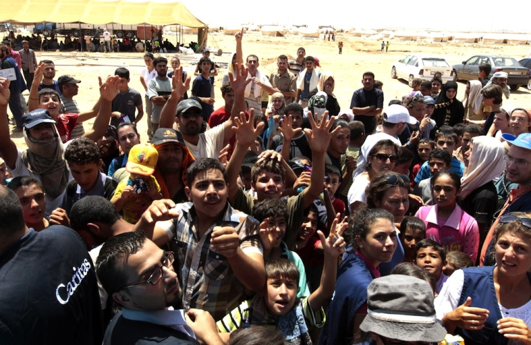 <p>Syrian refugee children receive aid distributed by an aid organization at the Zaatari refugee camp, located outside the northern Jordanian city of Mafraq, near the border with Syria, on August 15, 2012.</p>