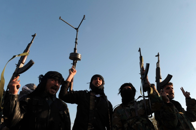 <p>Members of the Free Syrian Army hold up their weapons in Syria's northwest on February 18, 2012.</p>