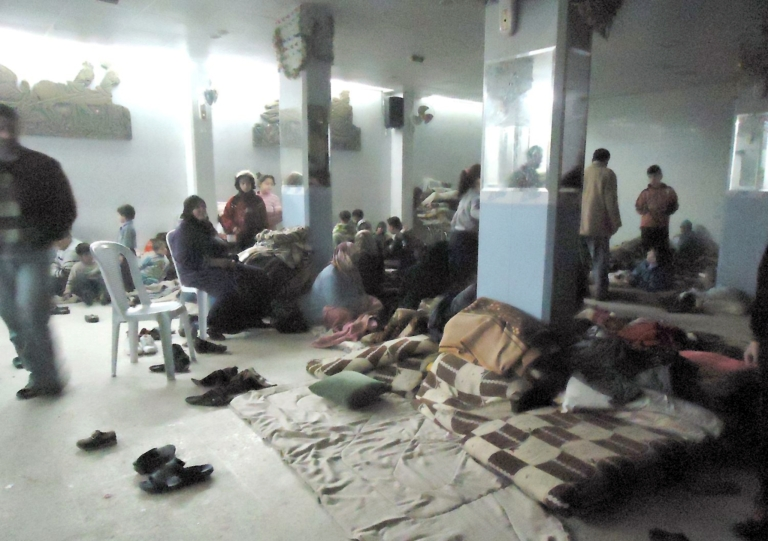 <p>Syrian families hide in a shelter near Baba Amr neighborhood in Homs on Monday.</p>