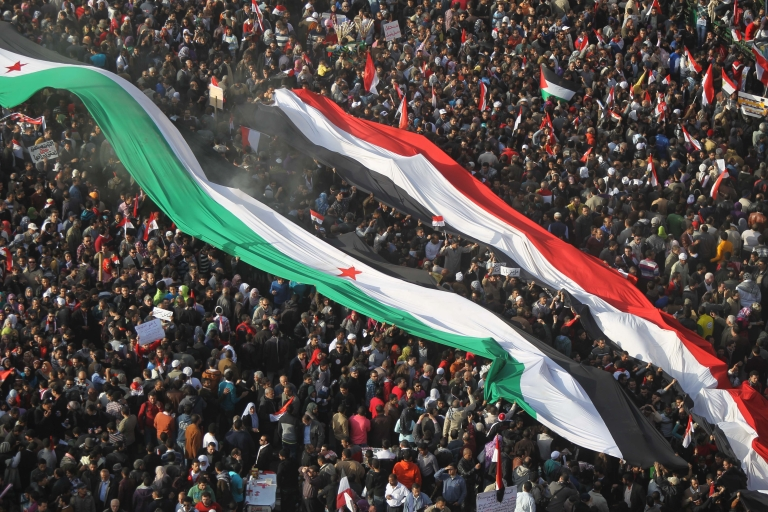 <p>Egyptian protesters hold up giant national and Syrian flags during a rally in Tahrir Square on January 25, 2012, on the first anniversary of the country's revolt against the former regime. AFP PHOTO / KHALED DESOUKI</p>