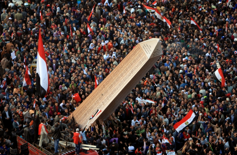 <p>Egyptian protesters carry an obelisk with the names of those killed during last year's uprising, at a huge rally in Tahrir Square on January 25, 2012, marking the first anniversary of the uprising that toppled president Hosni Mubarak as a debate raged over whether the rally was a celebration or a second push for change. AFP PHOTO/MAHMUD HAMS</p>