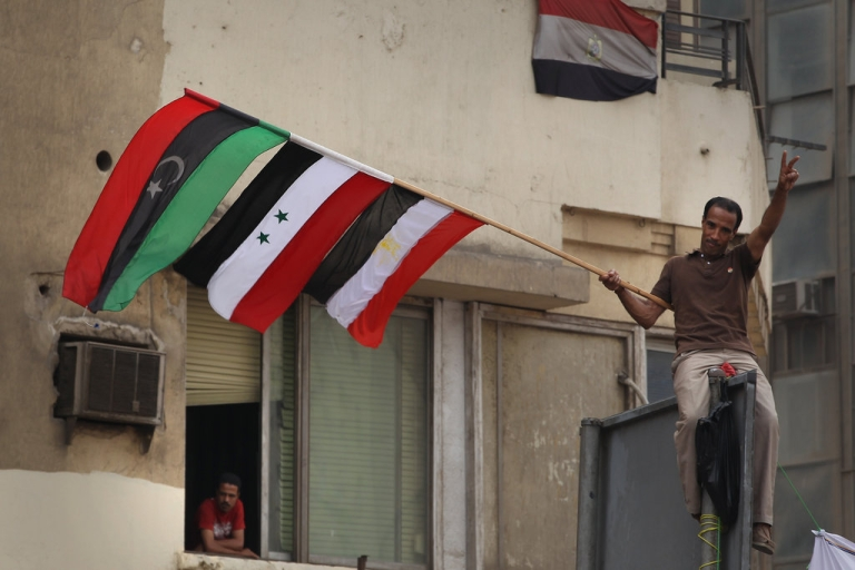 <p>A demonstrator waves an Egyptian, Syrian and Libyan flag in Tahrir Square on May 27, 2011 in Cairo, Egypt. The ruling Supreme Council of the Armed Forces said that there would be no use of violence against protests dubbed 'the Second Revolution of Anger' taking place in Cairo and other cities in Egypt.</p>