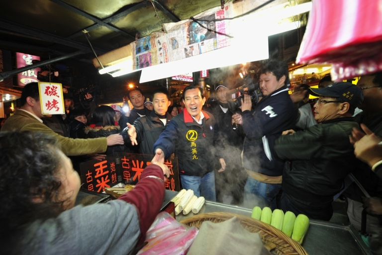 <p>Taiwan President Ma Ying-jeou (C) shakes hands with a food stall worker in Keelung City on Jan. 11, 2012.</p>