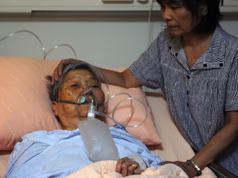 <p>Wang Ho-shou, 94 is cared for by a member of her family at a local hospital following a fire at a nursing home in Tainan, southern Taiwan, on October 23, 2012.</p>