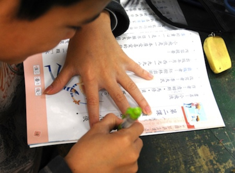 <p>An elementary school student takes notes during class in Taipei, Taiwan's capital, in February 2010.</p>