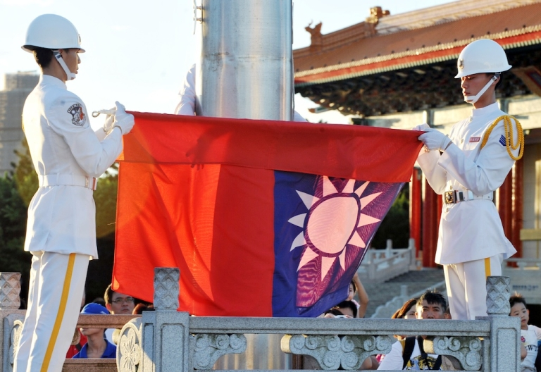 <p>Two members of the Taiwan Navy honour guard fold up Taiwan's national flag during a ceremony in the capital Taipei on July 28, 2012.</p>