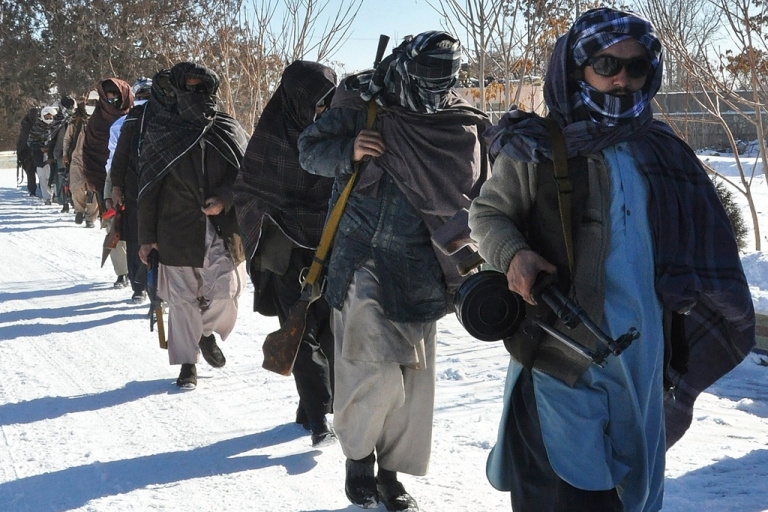 <p>Taliban fighters walk with their weapons after joining Afghan government forces for a ceremony in Ghazni province on Jan. 16, 2012.</p>