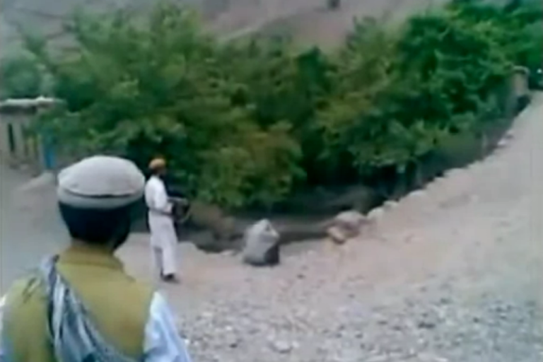 <p>This screenshot shows a member of the Taliban shooting a woman (huddled) at point-blank range, while others look on.</p>
