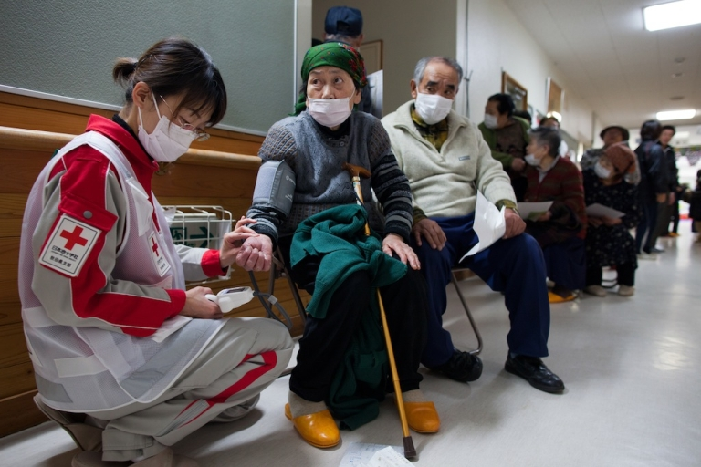 <p>Medical staff from the Japanese Red Cross treats earthquake victims at a medical clinic in an evacuation center where hundreds of homeless are staying March 21, 2011, in Rikuzentakata, Japan.</p>