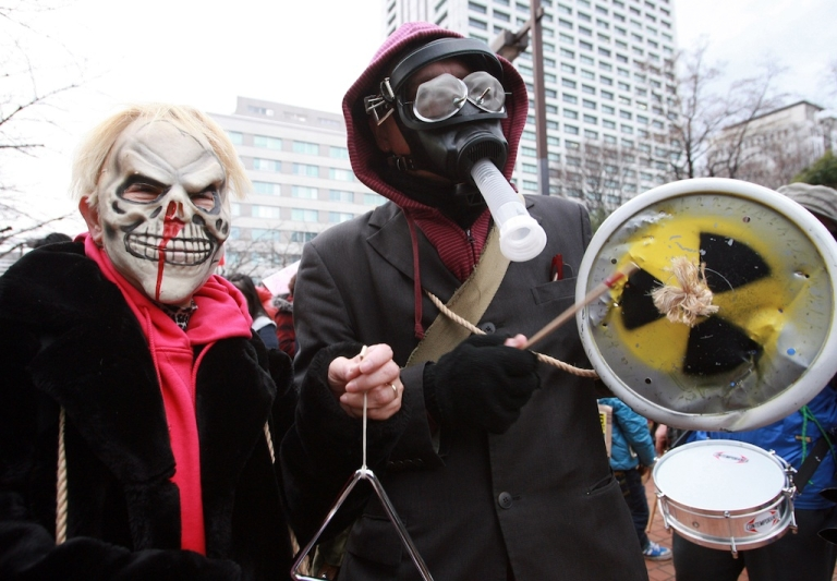 <p>Anti-nuclear protesters wear masks during a demonstration outside Tokyo Electric Power Company's headquarters in Tokyo on March 11, 2012, on the first anniversary of the earthquake and tsunami which triggered a meltdown at the company's Fukushima Daiichi nuclear power plant.</p>