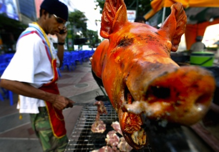 <p>A Thai cook flips pork cutlets below a whole roasted pig while talking on a mobile phone at a Bangkok beer garden.</p>
